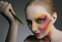 Woman wearing strong make-up, holding a piece of aloe