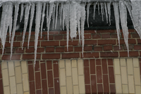 Icicles formed on wall of bricks, low angle view