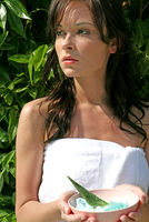 Woman wearing a towel holding spa botanicals