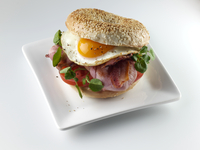 Breakfast bagel with fried egg bacon and tomato editorial food