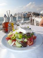 Greek salad and al fresco dining scene on the Greek island of Mykonos, Greece