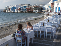 Two young women enjoying the view from an al fresco restaurant on the Greek Island of Mykonos, Greece 20025327097| 写真素材・ストックフォト・画像・イラスト素材|アマナイメージズ