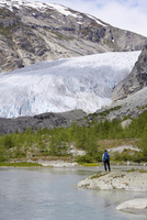 Norway, Nigardsbreen, Glacier tongue, Hiker on shore, rear view