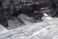 Norway, Nigardsbreen, Tourists walking across glacier tongue