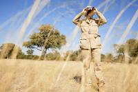 Africa, Botswana, Okavango Delta, Man looking through binoculars 20025327651| 写真素材・ストックフォト・画像・イラスト素材|アマナイメージズ