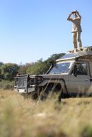 Africa, Botswana, Okavango Delta, Man on safari using binoculars 20025327656| 写真素材・ストックフォト・画像・イラスト素材|アマナイメージズ