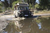 Africa, Botswana, Okavango Delta,Vehicle crossing waterhole 20025327665| 写真素材・ストックフォト・画像・イラスト素材|アマナイメージズ