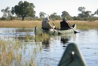 Africa, Botswana, Okavango Delta, Men in canoe 20025327667| 写真素材・ストックフォト・画像・イラスト素材|アマナイメージズ