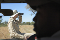 Africa, Botswana, Man looking through binoculars 20025327671| 写真素材・ストックフォト・画像・イラスト素材|アマナイメージズ
