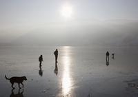 Austria, Salzkammergut, People walking on frozen lake