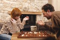 Couple playing backgammon, fireside in background 20025328074| 写真素材・ストックフォト・画像・イラスト素材|アマナイメージズ