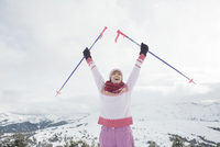 Italy, South Tyrol, Seiseralm, Woman holding ski poles, cheering, portrait