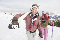 Italy, South Tyrol, Seiseralm, Couple carrying skis, smiling, portrait