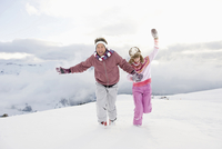 Italy, South Tyrol, Seiseralm, Couple running in snow, laughing