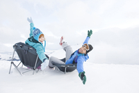 Italy, South Tyrol, Seiseralm, Couple in winter clothes sitting on chairs, fooling about