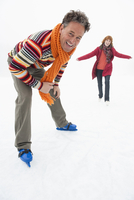 Italy, South Tyrol, Seiseralm, Woman ice skating, man in foreground, laughing, portrait