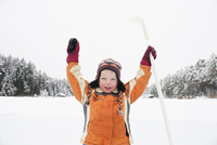 Italy, South Tyrol, Seiseralm, Boy (4-6) holding hockey stick, cheering, portrait