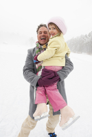 Italy, South Tyrol, Seiseralm, Father holding daughter (4-5) smiling, portrait, close-up