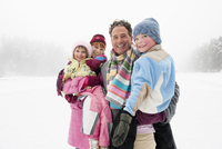 Italy, South Tyrol, Seiseralm, Family on frozen lake, portrait, close-up