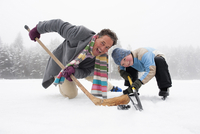 Italy, South Tyrol, Seiseralm, Father and son (4-5) playing ice hockey, smiling, portrait