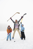 Italy, South Tyrol, Seiseralm, Father and children (4-5) standing on frozen lake, holding hockey sticks, cheering