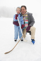 Italy, South Tyrol, Seiseralm, Father and son (4-5) holding hockey sticks, smiling, portrait