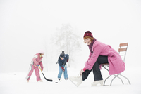 Italy, South Tyrol, Seiseralm, Woman sitting on chair, children (4-5) playing ice hockey on frozen lake 20025328193| 写真素材・ストックフォト・画像・イラスト素材|アマナイメージズ