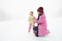 Italy, South Tyrol, Seiseralm, Mother and daughter (4-5) on frozen lake, wearing ice skates