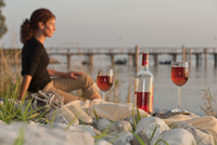 Germany, Meersburg, Mature woman at beach with enjoying a glass of wine