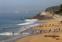 India, South India, Kerala, Malabar Coast, Fishermen pulling net on beach near Kovalam, Vizhinjam in background