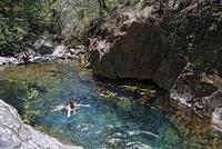 Costa Rica, Guanacaste, Rincon de la Vieja National Park, Tourists bathing in stream