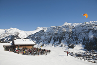 Austria, Vorarlberg, Lech am Arlberg, People skiing and paragliding near ski hut in winter