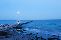 Italy, Friuli, Grado, Person on beach during full moon at night