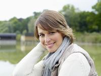 Germany, Munich, Mature woman in warm clothing near lake, smiling, portrait