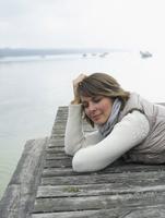 Germany, Munich, Mature woman lying on jetty near lake, smiling 20025328674| 写真素材・ストックフォト・画像・イラスト素材|アマナイメージズ
