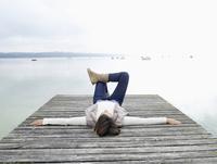 Germany, Munich, Mature woman lying on jetty near lake 20025328675| 写真素材・ストックフォト・画像・イラスト素材|アマナイメージズ
