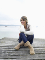 Germany, Munich, Mature woman sitting on jetty near lake, smiling 20025328678| 写真素材・ストックフォト・画像・イラスト素材|アマナイメージズ