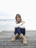 Germany, Munich, Mature woman sitting on jetty near lake, smiling, portrait 20025328679| 写真素材・ストックフォト・画像・イラスト素材|アマナイメージズ