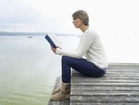 Germany, Munich, Mature woman sitting on jetty near lake and reading book 20025328681| 写真素材・ストックフォト・画像・イラスト素材|アマナイメージズ