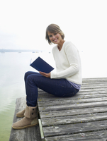 Germany, Munich, Mature woman sitting on jetty near lake and reading book, smiling, portrait 20025328683| 写真素材・ストックフォト・画像・イラスト素材|アマナイメージズ