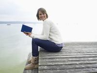 Germany, Munich, Mature  woman sitting on jetty near lake holding book, smiling 20025328684| 写真素材・ストックフォト・画像・イラスト素材|アマナイメージズ