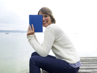 Germany, Munich, Mature woman sitting on jetty near lake and reading book, smiling, portrait 20025328685| 写真素材・ストックフォト・画像・イラスト素材|アマナイメージズ