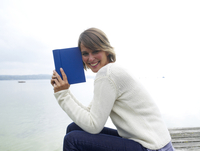 Germany, Munich, Mature woman sitting on jetty near lake and reading book, smiling, portrait 20025328686| 写真素材・ストックフォト・画像・イラスト素材|アマナイメージズ
