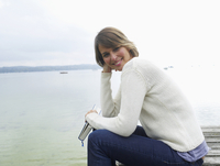 Germany, Munich, Mature woman sitting on jetty near lake and reading book, smiling, portrait 20025328687| 写真素材・ストックフォト・画像・イラスト素材|アマナイメージズ