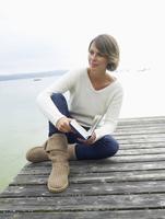 Germany, Munich, Mature woman sitting on jetty near lake holding book, smiling 20025328688| 写真素材・ストックフォト・画像・イラスト素材|アマナイメージズ