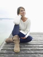 Germany, Munich, Mature woman sitting on jetty near lake holding book, smiling 20025328690| 写真素材・ストックフォト・画像・イラスト素材|アマナイメージズ