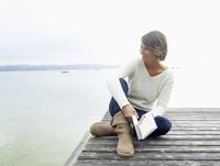 Germany, Munich, Mature woman sitting on jetty near lake holding book, smiling 20025328691| 写真素材・ストックフォト・画像・イラスト素材|アマナイメージズ