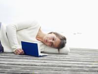 Germany, Munich, Mature woman lying on jetty near lake reading book 20025328693| 写真素材・ストックフォト・画像・イラスト素材|アマナイメージズ