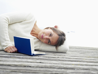 Germany, Munich, Mature woman lying on jetty near lake reading book, smiling, portrait 20025328694| 写真素材・ストックフォト・画像・イラスト素材|アマナイメージズ