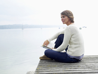 Germany, Munich, Mature woman sitting on jetty near lake and holding book, smiling, portrait 20025328701| 写真素材・ストックフォト・画像・イラスト素材|アマナイメージズ